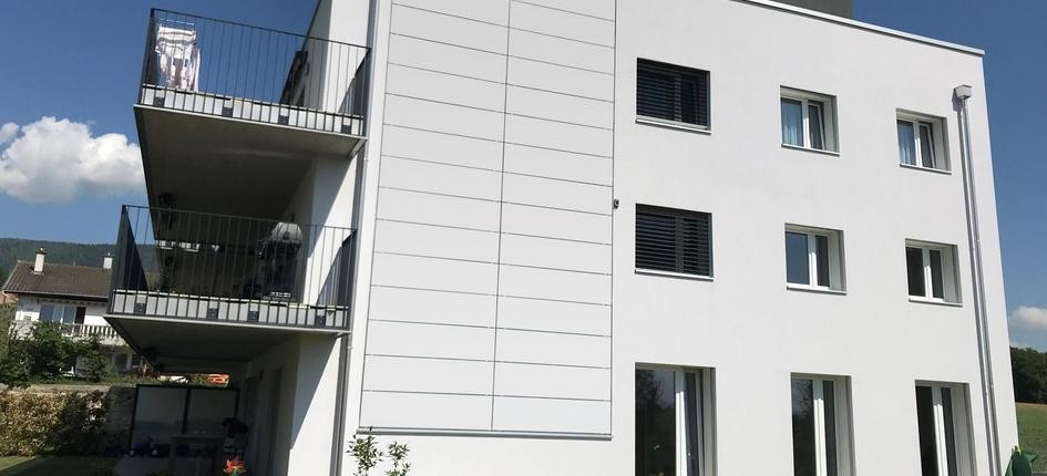 White photovoltaic modules on a building facade can be integrated almost seamlessly into the architectural design.